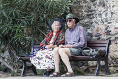 The talker and the listener (Frank Fullard) Tags: frankfullard fullard candid street portrait story storytelling talk listen pair couple partient hearing colour older elderly bench collioure france resort tale park sitting resting gossip frock hat