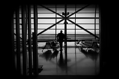 an international airport (KIX Japan) (明遊快) Tags: airport bw city urban man window shadows light blackandwhite lines contrast reflections mono design kix japan dusk evening