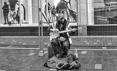 Deliverance (tcees) Tags: x100 fujifilm finepix bw mono monochrome blackandwhite sidewalk pavement kerb fence outdoor daytime tarletonstreet liverpool bag banjo man cap hat coat bottle ms shop store pictures adverts busker streetphotography street mannequins musicalinstrument