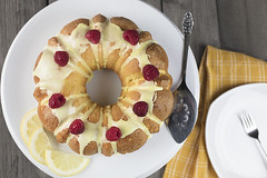 Lemon cake frosted with yellow sugar icing and red raspberries, dressed with lemon slices on the side on a white platter (Transient Eternal) Tags: baking bake cake pastry confection foodpreparation dessert desserts sweets creamy batte slices birthdaycake raspberries red fruit lemon lemonslices cuisine gourme lemoncake yellowcake spongecake frosting sugary sugar texture golden partyfood vintage tabletop gettogether yummy goodfood plated serving spatula bakedgoods vanilla