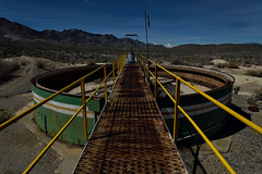 walk the plank. mojave desert, ca. 2016. (eyetwist) Tags: eyetwistkevinballuff eyetwist night goldmill chemical tanks toxic superfund abandoned sky glow ruins gold mill mine mining ore machinery equipment industry industrial factory urbex mojavedesert nikon nikond7000 d7000 nikkor capturenx2 1024mmf3545g fullmoon desert dark longexposure moonlit gel npy nocturne highdesert mojave california long exposure wideangle forgotten ruin decay architecture building exploring saturated graphic dangerous green girder tank startrails goldome cyanide storage waste spooky haunted ghosts vanishingpoint landscape geometric gangplank walkway