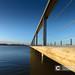 Concrete pedestrian bridge with metal railing in perspective.