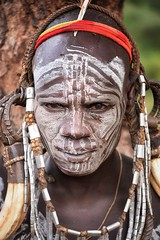 Mursi Warrior  (explore) (Rod Waddington) Tags: africa african afrique afrika äthiopien ethiopia ethiopian ethnic etiopia ethnicity ethiopie etiopian omovalley omo outdoor omoriver mursi tribe traditional tribal culture cultural warrior man tree beads portrait painted face feather village