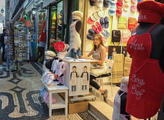 Embroidery in Lisbon (Marian Pollock) Tags: europe lisbon portugal girl embroidery shop street sowing shopfront slippers aprons bibs hats balls people candid childrenswear footpath paving display