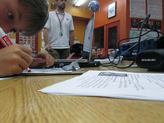 IMG_3825 (classroomcamera) Tags: classroom school desk table wood paper writing drawing background foreground brown tan orange wires watch focus