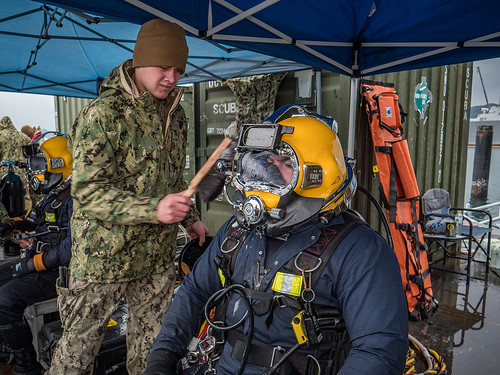 U.S. Navy construction mechanics prepare to conduct an underwater pile removal at Commander, Fleet Activities Sasebo