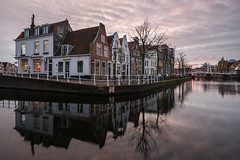 Daylight Saving (McQuaide Photography) Tags: haarlem noordholland northholland netherlands nederland holland dutch europe sony a7rii ilce7rm2 alpha mirrorless 1635mm sonyzeiss zeiss variotessar fullframe mcquaidephotography lightroom adobe photoshop tripod manfrotto light licht water reflection stad city urban waterside lowlight architecture outdoor outside waterfront building river spaarne riverside traditional authentic skyline house houses huis huizen residential longexposure calm still nopeople old oldhouse dutcharchitecture kortespaarne sunset zonsondergang sky lucht