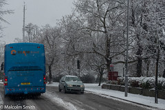 Snow Coach (M C Smith) Tags: coach snowing pentax k3 aerial pavement kerb slush sign blue grey branches trees lights letters numbers symbols lamps mirrors hedge wall