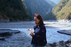 Faye Eating Octopus by the Choshui River (Bob Hawley) Tags: asia taiwan nikond7100 nantoucounty xinyidistrict nikkor35135mmf3545lens outdoors nature mountains no16provincialhighway choshuiriver dilivillage valleys people women portraits