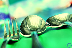 while waiting for the food to be served... (NadzNidzPhotography) Tags: nadznidzphotography smileonsaturday shinymetals utensils fork spoon green party bokeh shallowdepthoffield shapes spoonart