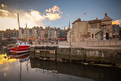 "La Lieutenance restored perches by the water access to le Vieux Bassins (Old Harbour) at sunset in autumn, Honfleur, Calvados, Normandy, France (grumpybaldprof) Tags: ""vieuxbassin"" ""oldharbour"" honfleur normandie normandy france ""quaistecatherine"" ""quaiquarantaine"" quai ""quaistetienne"" ""stecatherine"" ""lalieutenance"" quarantaine water boats sails ships harbour historic old ancient monument picturesque restaurants bars town port colour lights reflection architecture buildings mooring sailing stone collombage halftimbered yachts carousel merrygoround reflections ""waterreflections ""wetreflections""funfair ""eglisesaitecatherine"" yacht voillier calvados ""fineart"" striking artistic interpretation impressionist stylistic style colours colourful bright sunset october autumn sunlight history blue sky canon 70d ""canon70d"" sigma 1020 1020mm f456 ""sigma1020mmf456dchsm"" ""wideangle"" ultrawide"