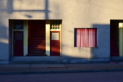 In Fred Herzog's shadow (James_D_Images) Tags: vancouver britishcolumbia mainstreet 2nd avenue old apartment building stucco red door faded pink curtain window sidewalk shadow stairs yellow doorframe peeling weathered inspiration inspiredby fredherzog photography history