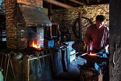 Blacksmithing (Matt Molloy) Tags: mattmolloy photography blacksmith person working metal hot glowing orange fire shaping hammering sparks stone old tools anvil bricks fireplace historic building 1843 jonesfalls ontario canada lovelife