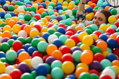 Drowing in the ball pit (Josiedurney) Tags: summer eastlondon summerinthecity londonlife fun hipster cool birthday towerhamlets university colour ballpit balls child children play boxpark shippingcontainer shoreditch girl cute smile camera action