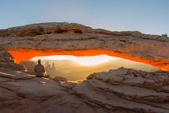 Enjoying the Sunrise Under Mesa Arch (NickSouvall) Tags: canyonlands canyon cliff rocks geology mesa arch view hike viewpoint sunrise morning orange glow yellow clear sky blue adventure landscape moab utah arches nature photography explore discover picture photo photographer sun rays beam light warm color colorful