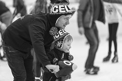 Ice stakers (Frank Fullard) Tags: frankfullard fullard candid street portrait family father son penguin ice skating monochrome blackandwhite castlebar mayo irish ireland happy christmas festive face cap knitted smile dad helping