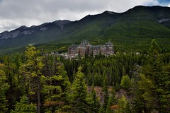 Nestled in a Hillside of Evergreens and Sulphur Mountain as a Backdrop (Banff National Park) (thor_mark ) Tags: nikond800e lookingssw day2 triptoalbertaandbritishcolumbia banffnationalpark capturenx2edited colorefexpro surprisepoint surprisecorner banffspringshotel sulphurmountain rockymountains canadianrockies southerncontinentalranges southbanffranges outside nature landscape overcast mountains mountainsindistance mountainsoffindistance mountainside hillsides trees hillsideoftrees evergreens hotel canadianflag flag flagpole portfolio project365 banff alberta canada