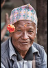Man in a topi with tikka during Dasain holiday, Kathmandu, Nepal (jitenshaman) Tags: travel destinations worldlocations asia asian nepal nepali kathmandu topi nepalitopi hat hats cap traditional smile flower portrait happy pose tikka dasain dashain tihar man male grandfather grandpa old wrinkles face