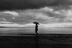 Afternoon promenade by the sea (tzevang.com) Tags: umbrella bw seashore promenade shillouete lakonia greece black bythesea sea