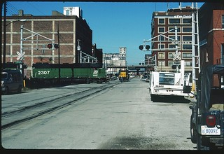 BN 2307 has the right-of-way against that CNW light motor on Santa Fe Street in the West Bottoms of Kansas City, Missouri October 1986