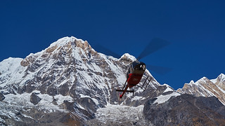 Helicopter flying in front of Annapurna South (Dakshin), Annapurna massif, Nepal