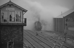 The Box Bobby looks on as 60009 'Union of South Africa' emerges from the Goods Loop and a cloud of steam after a water stop. The Christmas White Rose Tour, Cambridge to York. 20 12 2017 bw (pnb511) Tags: a4 60009 steam loco locomotive engine track signal box semaphore pacific line train railway branch mist dull winter