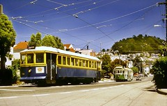 Vintage Trolley Cars (en tee gee) Tags: sanfrancisco trolley streetcar 1989 catenary trolleywire street houses california trees sky