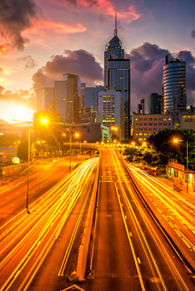 Traffic at central district in Hong Kong at sunrise time. Car light trails and urban cityscape in Hong Kong .