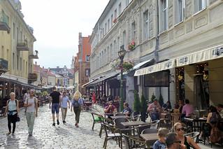 DSC_5686 Fussgängerzone / Vilniaus in Kaunas - Touristen schlendern in der Sonne; Aussengastronomie - Restaurants und Cafés, Tische mit Gästen an der Straße.