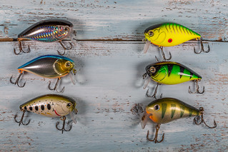 Colorful fishing lures on the wooden background