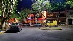 Calor - Warmth (Raúl Alejandro Rodríguez) Tags: rarb1950 noche night calle street restaurant pub autos cars árboles trees urban cartel luminoso letrero sign neon sillas chairs mesas tables buenos aires argentina