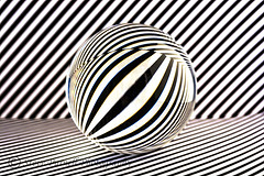 Crystal Amaze (Steve Purnell Photography) Tags: crystalball crystal glassball glass ball round circle circular opticalart opart art stripes blackandwhitestripes blackstripes whitestripes refraction opticalillusion opticaleffect magic reflection shiny sphere globe magical magicball mysterious orb photo studioshot mystic surreal futuristic modern abstract