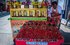 2017 - Mexico - Zihuatanejo - Strawberry Man (Ted's photos - For Me & You) Tags: 2017 cropped mexico nikon nikond750 nikonfx tedmcgrath tedsphotos tedsphotosmexico vignetting zihuatanejo streetscene street cart strawberries fruit bienfrio shadow red redrule apron sandal pineapple