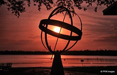 Centered on the Sun (pandt) Tags: kissimmee florida armillary sun sunrise sunlight water lakebrown lake sky clouds trees orange yellow outdoor landscape canon eos 7d slr