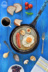 Directly Above Shot Of Fried Egg With Sausage and Onion In Saucepan. Blue wooden background (Food photography / Food styling) Tags: closeup colorimage farmer fleshy foodanddrink foodbackground idea largegroupofobjects photography ruralscene saturated sliced vertical wallpaper agriculture basil blue bread breakfast coffee day dinner egg fresh fried healthy lunch meat natural nature nutrition olives onion organic piece plant red restaurant sausage slice slicesofbread summer tasty tomato top vegetable