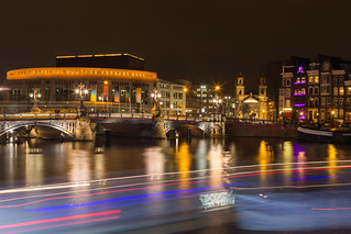 Stopera and Blue Bridge  crossing the Amstel river at night in the Amsterdam city center
