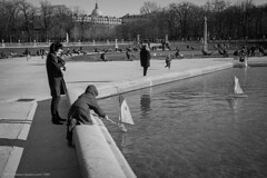 Yachting on the Lake (gwpics) Tags: france winter relaxation child paris french play people jardinduluxembourg streetphotography outside family mono children yacht everydaylife film leica lifestyle monochrome person socialcomment socialdocumentary society streetphotos streetpics bw blackwhite blackandwhite exterior kids outdoors streetlife