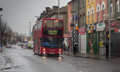 A Wet Day In Leyton 2 (M C Smith) Tags: bus red letters numbers symbols 158 route leyton stagecoach lines white pink yellow orange crossing roadworks cones salmonpink green blue cars van parking wet rain umbrellas signs grey sky lamps shops buses houses