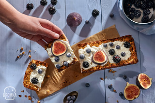 Hand picking piece of oatmeal cake with natural yogurt, honey, fresh figues, blackberries and blueberries