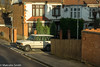 Classic 4-Door (M C Smith) Tags: rangerover junction white pentax k3 pavement kerb lines yellow wall fence wooden trees hedges green weeds houses shadows lamp aerial dish signs