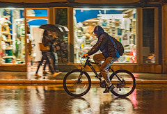 Cyclist in the Rain (fotofrysk) Tags: cyclist pedestrians shops storewindows istarskastreetwet with rainumbrellabikebicycleeastern europe tripcroatiapulaistriadalmatian coastsigma 1750mm f28 ex dc ox hsmnikon d7100 201710038044