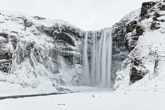Skogafoss in Winter II (B.E.K. Photography) Tags: iceland skogafoss waterfall water sky clouds mountain cliff ice snow icicle long exposure winter river stream white nikon d850 1735 f28 rock hikey