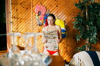 Woman in red bikini during summer reads the newspaper