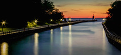 Looking down the Channel to the Sunset (T P Mann Photography) Tags: charlevoix michigan channel river water reflections color lights long exposure lighthouse pier railings sunlit sundown sunset evening red canon orange landscape sea seascape horizon