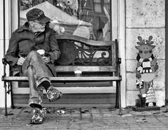 Where's Santa (Anne Worner) Tags: man older beard coffee bench jeans jacket cap glasses lonestar sitting displaywindow reflectionseasonal woodenreindeer wall pavement em5 olympus anneworner street streetphotography bw blackandwhite mono norway