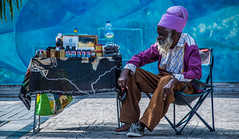 2017 - Regent Cruise - Martinique - Fort de France Street Vendor (Ted's photos - For Me & You) Tags: 2017 cropped martinique nikon nikond750 nikonfx regentcruise tedmcgrath tedsphotos vignetting fortdefrance seat seated male man headdress merchandise table wares beard chanflor chair