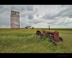 storm warning (Gordon Hunter) Tags: prairies tractor grass field crop grain elevator red old abandoned decay derelict weathered building tall storm sky clouds grey gray engine shed office shack dankin sk saskatchewan canada pool gordon hunter nikon d5000 summer 834 august 2010