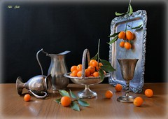 For Kumquat  Lovers (Esther Spektor - Thanks for 12+millions views..) Tags: stilllife naturemorte bodegon naturezamorta stilleben naturamorta composition creativephotography art winter tabletop food fruit kumquat branch silverware pitcher goblet tray basket metal pewter ambientlight reflection orange green grey silver brown black estherspektor canon fabuleuse