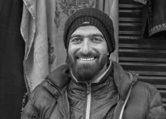 Portrait of a street vendor (tmeallen) Tags: streetvendor shopkeeper smiling man winter hat jacket headandshoulders mainbazaar leh ladakh jammuandkashmir northernindia