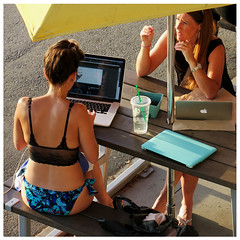 Laptops at the Beach (HereInVancouver) Tags: youngwomen beach bikini laptop computer fromabove vancouverswestend thingstodobythewater picnictable beachumbrella summer warm vancouver bc canada candid streetphotography englishbaypark